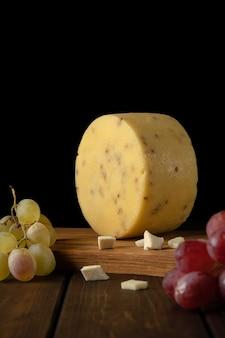 Kawałek okrągłego żółtego twardego sera ze słonecznikiem, gałązki czerwonych i zielonych winogron na desce do krojenia, zbliżenie, widok z boku