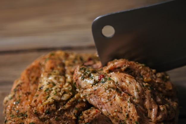 Kawałek pieczonego mięsa z grilla z przyprawami leży na drewnianej powierzchni z bliska