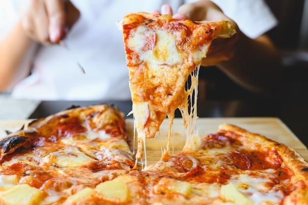 Kawałek pizzy na ognisko w dłoni. tradycyjna pizza hawajska i salami wytrawne danie pochodzenia włoskiej restauracji.