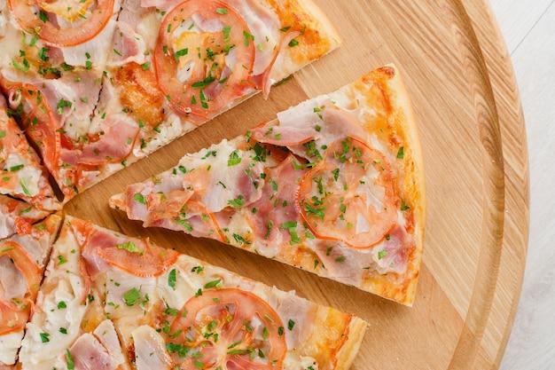 Kawałek pizzy z bliska na drewnianym biurku