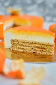 Kawałek pomarańczowego ciasta z polewą lustrzaną.