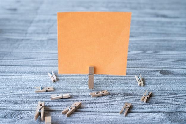 Kawałek pustej kwadratowej notatki otoczony spinaczami do prania pokazującymi nowe znaczenie pustego lepkiego papieru