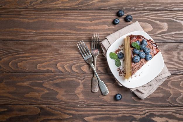 Kawałek pysznego biszkoptu z kremem i czekoladą na talerzu widok z góry