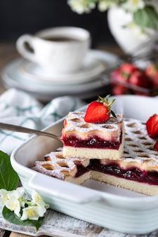 Kawałek pysznego ciasta jagodowego z truskawkami z filiżanką kawy na śniadanie. pionowy