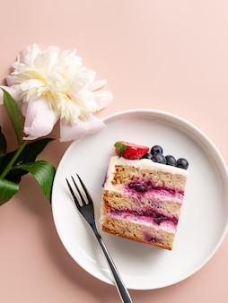 Kawałek pysznego ciasta z borówkowym nadzieniem i kwiatem piwonii słodkie warstwowe ciasto