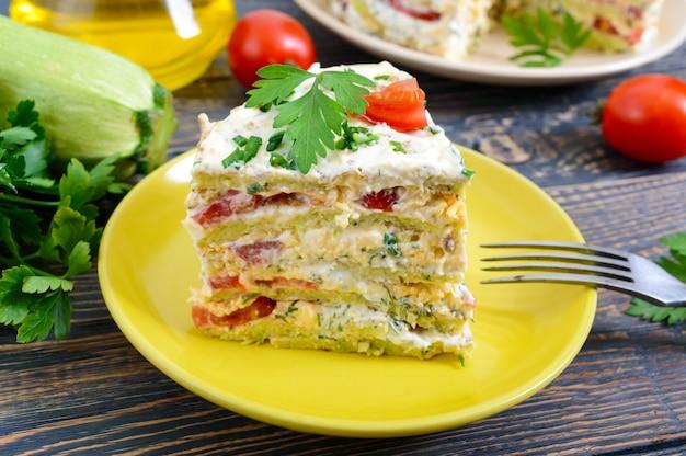 Kawałek pysznego ciasta z cukinii, pomidorów i sera na drewnianym stole. ciasto warzywne