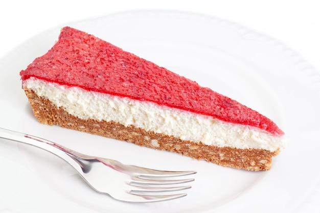 Kawałek pysznego ciasta z truskawkami i śmietaną na talerzu z widelcem.