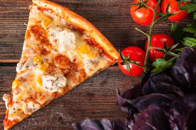 Kawałek pysznej pizzy podany na drewnianej powierzchni z wiśniami, pietruszką i bazylią, widok z góry