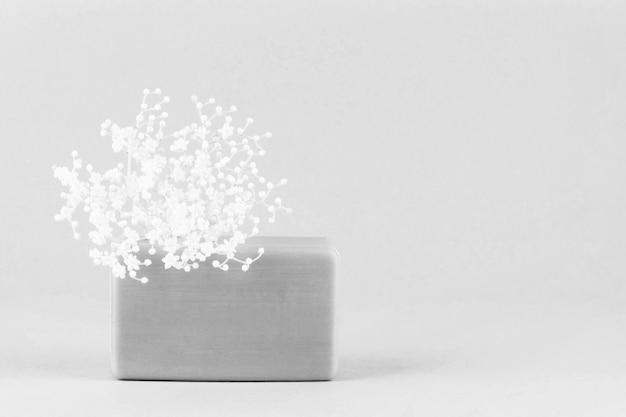 Kawałek ręcznie robionego mydła w białe kwiaty na jasnoszarym tle