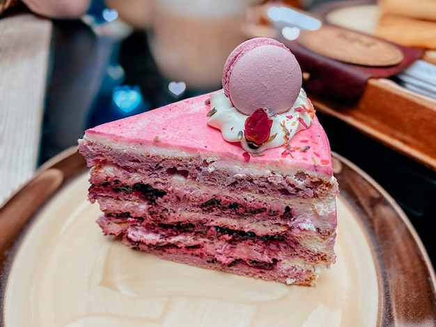 Kawałek różowego ciasta z biszkoptem, różowym kremem i dekoracją na wierzchu ciasta w postaci makaroników i suszoną różą na talerzu w restauracji.
