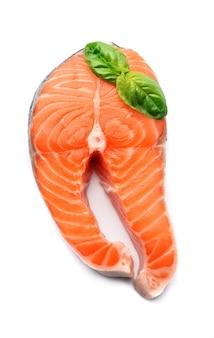 Kawałek ryby łososia z liśćmi bazylii na białym tle.