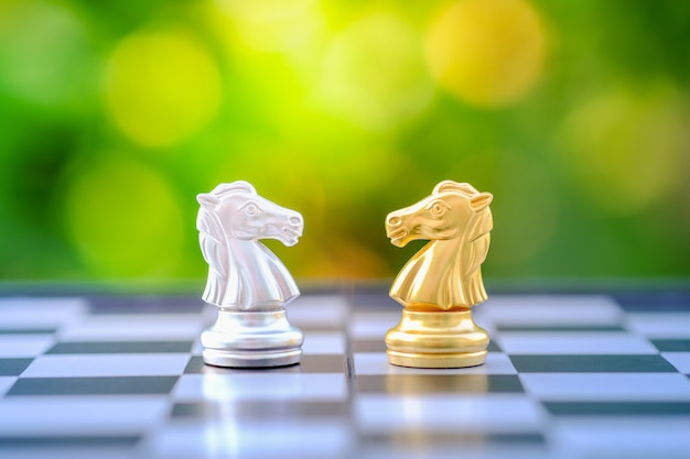 Kawałek rycerza ze złota i srebra na szachownicy.