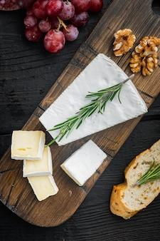 Kawałek sera brie na czarnym drewnianym stole, leżał na płasko