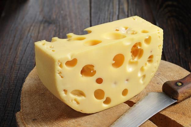 Kawałek sera i nóż na drewnianym tle