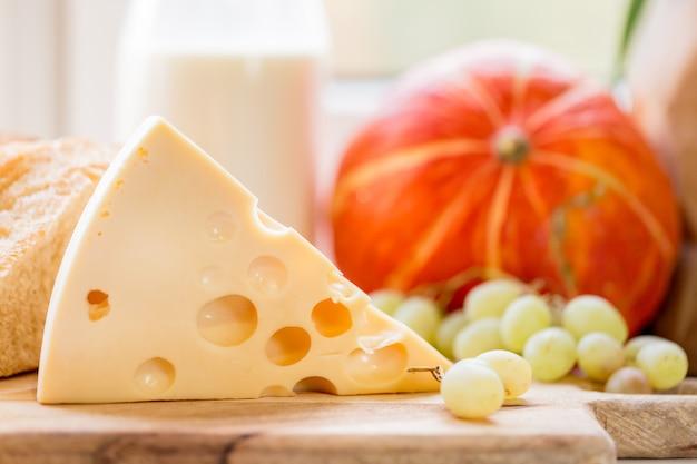 Kawałek sera i winogron na drewnianej desce z mlekiem i dynią