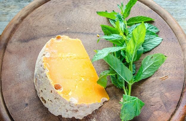 Kawałek sera mimolette z listkami mięty