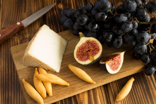 Kawałek sera, owoce i paluszki chlebowe na brązowej desce do krojenia