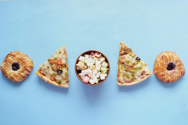 Kawałek sera pizza na talerzu, pączki i popcorn na niebiesko.