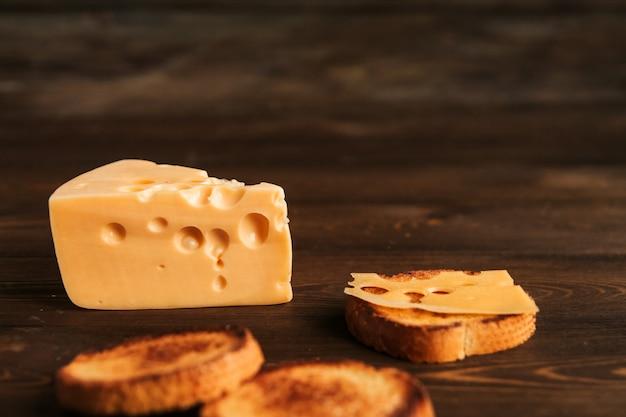 Kawałek sera z dużymi otworami i smażonym chlebem na drewnianym stole. kanapka z serem.