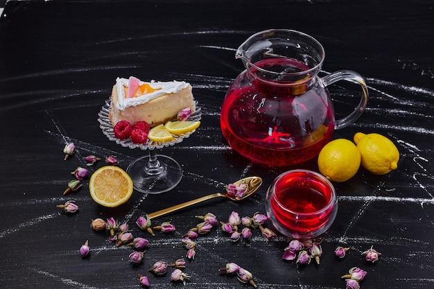 Kawałek sernika, cytryny i czarnej herbaty na stole z ciemnego marmuru.