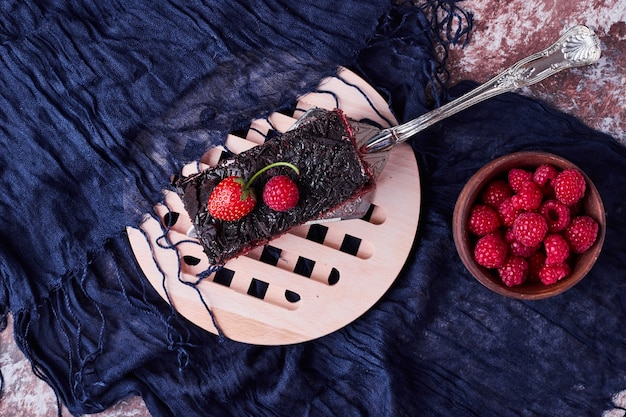 Kawałek sernika czekoladowego z jagodami.