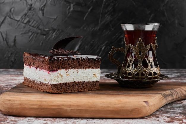 Kawałek sernika czekoladowego ze szklanką herbaty.