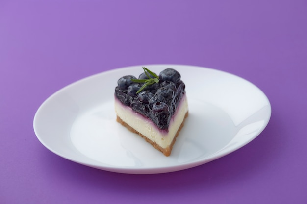Kawałek sernika jagodowego na białym talerzu na fioletowym tle