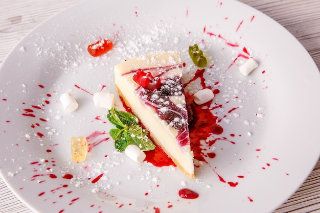 Kawałek sernika na białym talerzu do menu restauracji