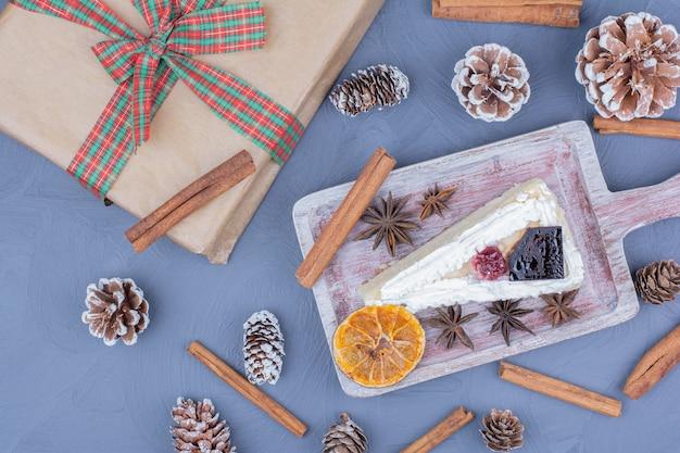 Kawałek sernika na drewnianym talerzu z kwiatami anyżu i laskami cynamonu