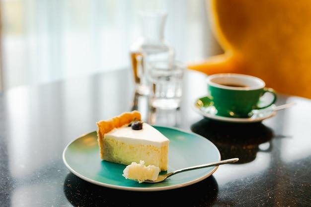 Kawałek sernika na niebieskim talerzu, widelec do deserów z małym kawałkiem ciasta, filiżanka czarnej kawy, karafka z wodą i szklanka, na czarnym stole