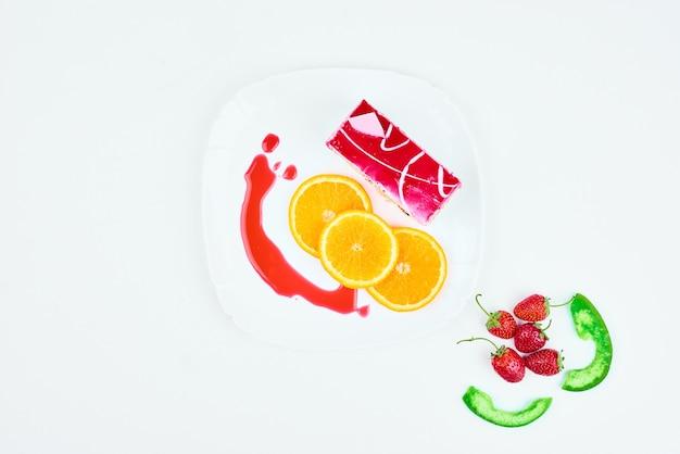 Kawałek sernika truskawkowego z owocami dookoła.