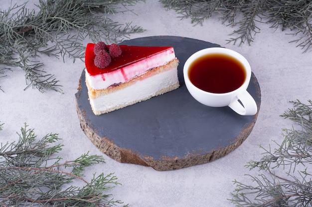 Kawałek sernika z filiżanką herbaty na drewnianym kawałku. zdjęcie wysokiej jakości