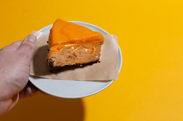 Kawałek sernika z mango z polewą z rokitnika w męskiej dłoni na pomarańczowym bezszwowym tle