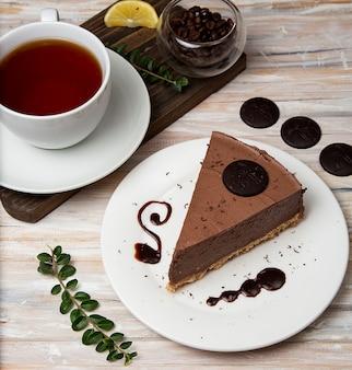 Kawałek sernika z musem czekoladowym z kawałkami czekolady i filiżanką herbaty.