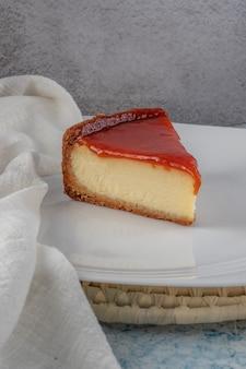 Kawałek sernika z pastą z guawy na białym talerzu na szarym i niebieskim tle.