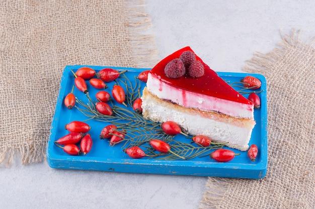 Kawałek sernika ze świeżych owoców dzikiej róży na niebieskim talerzu.