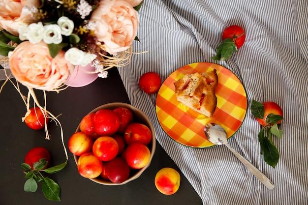 Kawałek śliwkowego ciasta na talerzu. letni przepis. martwa natura ze śliwkami i kwiatami.