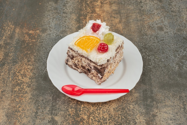 Kawałek słodkiego ciasta z czerwoną łyżką na białym talerzu