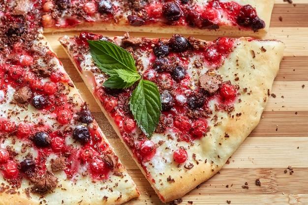 Kawałek słodkiej pizzy z porzeczką, czerwoną porzeczką, miętą i czekoladą