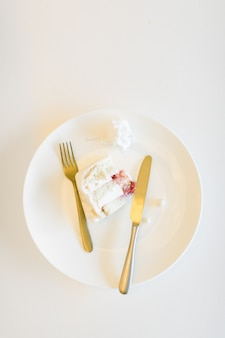 Kawałek ślubny tort w białym talerzu z haczyka i noża odgórnym widokiem na białej stołowej tło kopii przestrzeni dla teksta