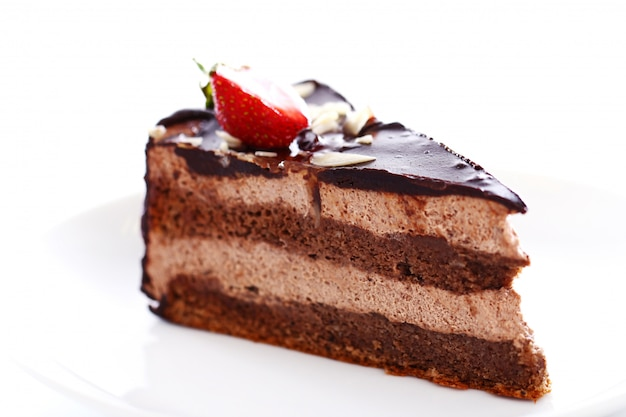 Kawałek smacznego ciasta czekoladowego z truskawkami na wierzchu