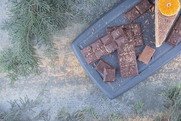 Kawałek smacznego ciasta z pokrojoną w plasterki czekoladą na ciemnej desce. zdjęcie wysokiej jakości
