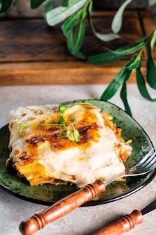 Kawałek smacznej gorącej lasagne z czerwonym winem. mała głębia ostrości. tradycyjna włoska lasagne. część. włoskie jedzenie. jedzenie na zielonym talerzu. sos boloński. sos beszamelowy. martwa natura z jedzeniem.