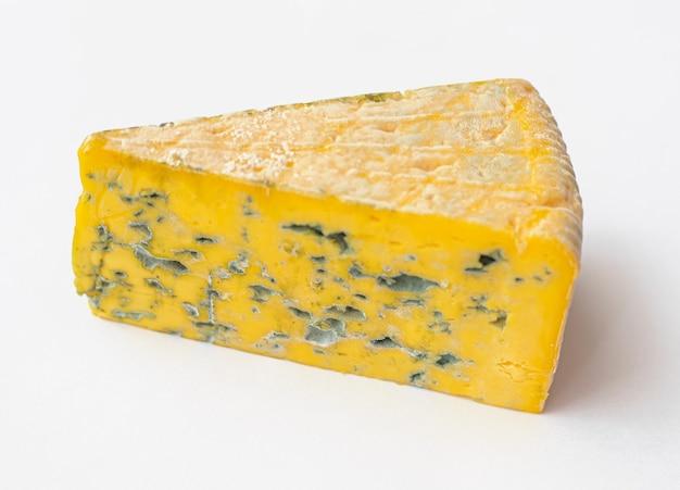 Kawałek spleśniałego sera na białym stole
