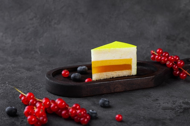 Kawałek sufletu cytrynowego na drewnianym talerzu, z jagodami i czerwoną porzeczką