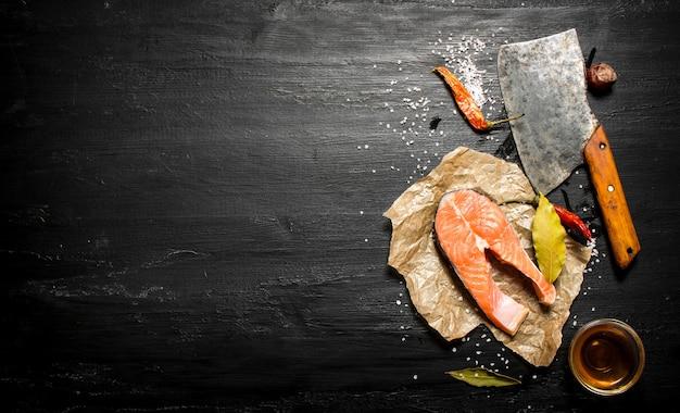 Kawałek surowego łososia z przyprawami i oliwą z oliwek. na czarnej tablicy.