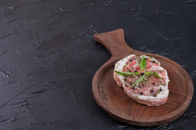 Kawałek surowego mięsa na drewnianym talerzu ozdobiony świeżą miętą na ciemnym tle.