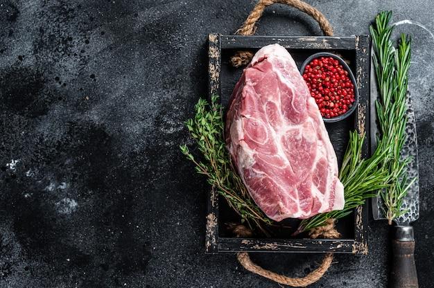Kawałek surowego mięsa z karkówki na chop steak na drewnianej tacy z ziołami. czarny