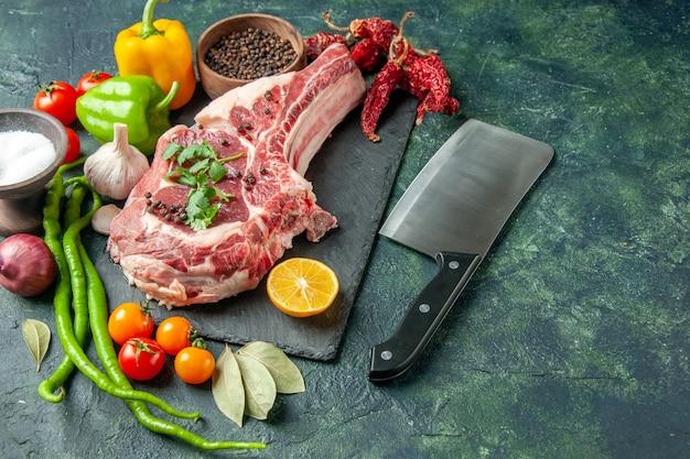 Kawałek surowego mięsa z widokiem z przodu ze świeżymi warzywami, solą i pieprzem na ciemnoniebieskiej powierzchni