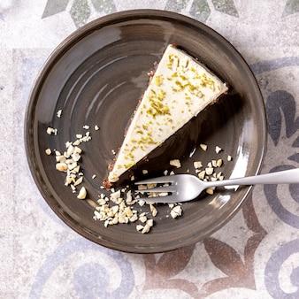 Kawałek surowego sernika wegańskiego bez glutenu, ozdobiony skórką z limonki i orzechami nerkowca na talerzu na ozdobnym ceramicznym stole. światło słoneczne. płaski układanie, przestrzeń. kwadratowy obraz
